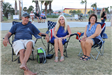 three adults sitting in lawn chair