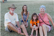grandparents and grandkids sitting on grass