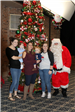 family smiling for photo with Santa
