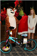 girl standing by new bike with rudolph and the grinch