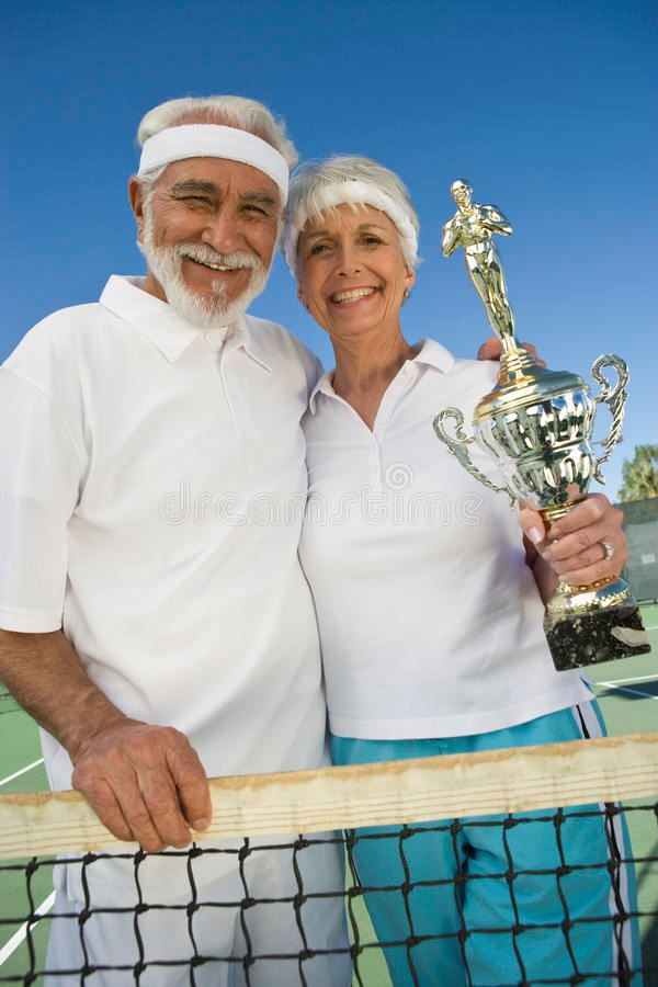 senior-couple-holding-trophy-tennis-net-29652344