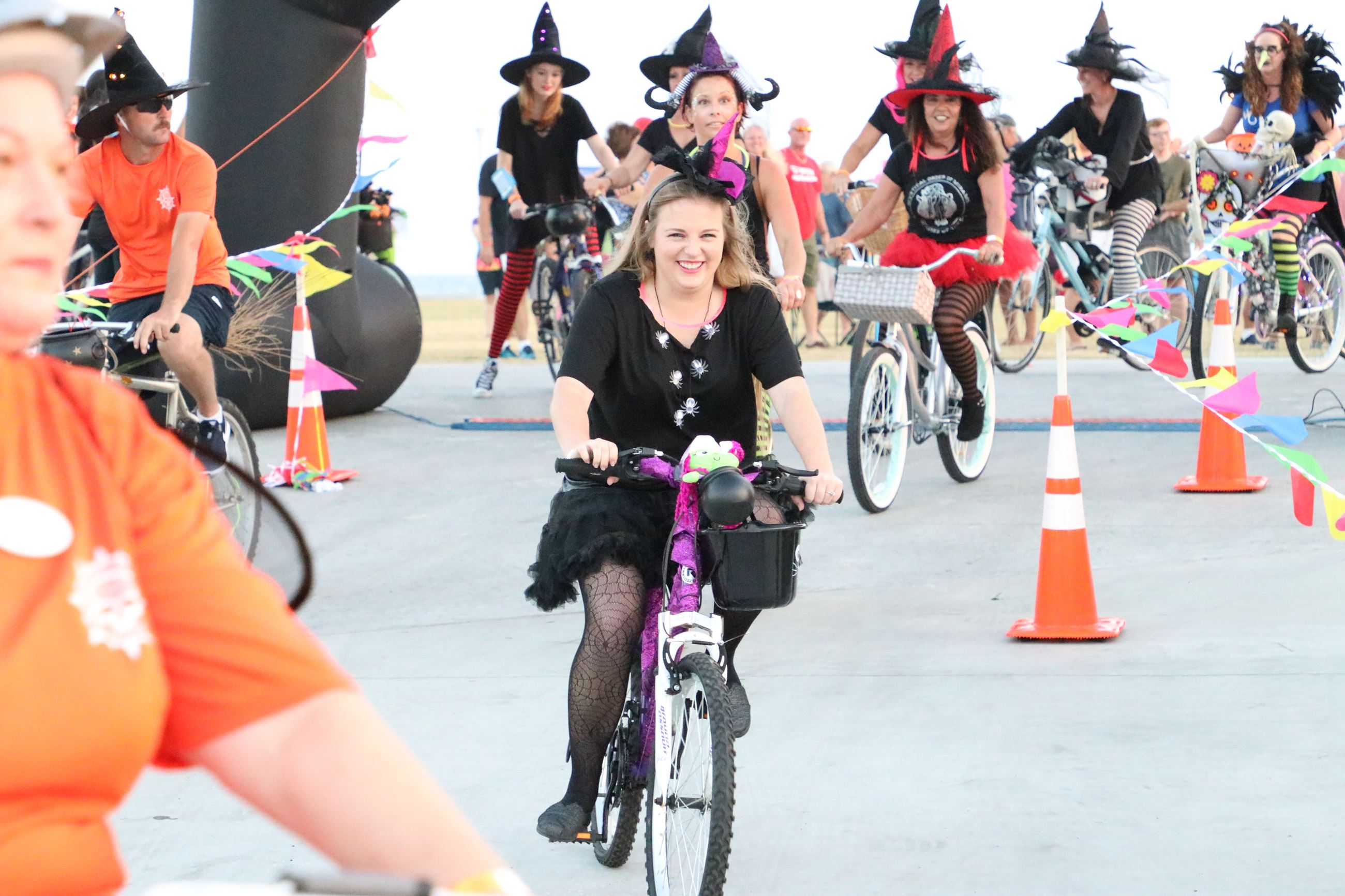 people dressed as witches riding bicycles