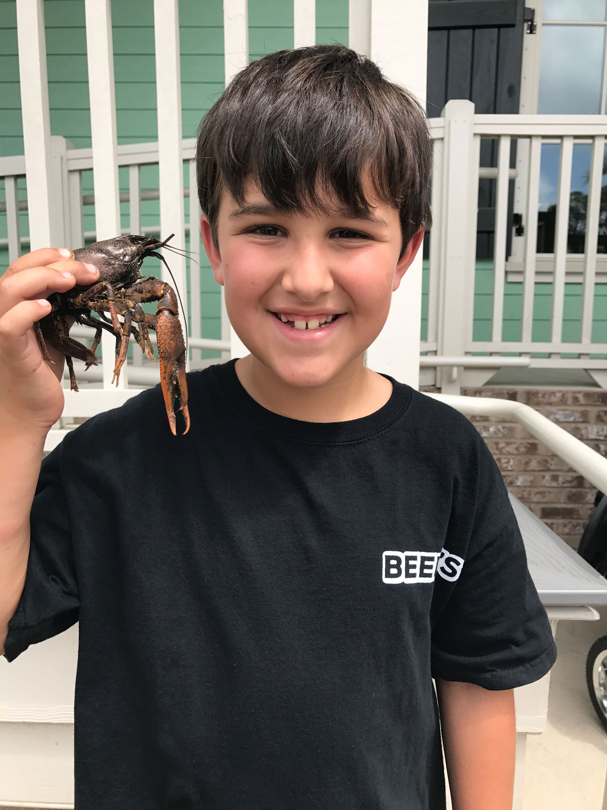 little boy holding a crawfish