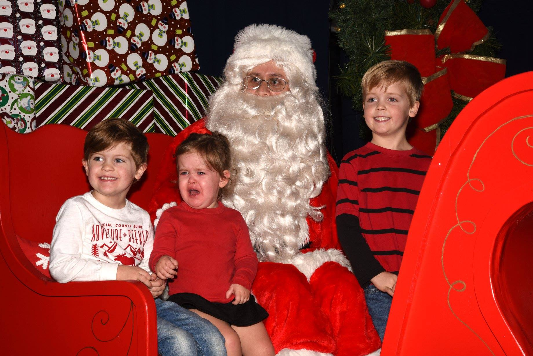 three kids sitting with Santa